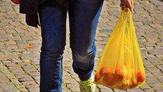 Un hombre camina llevando una bolsa de plástico