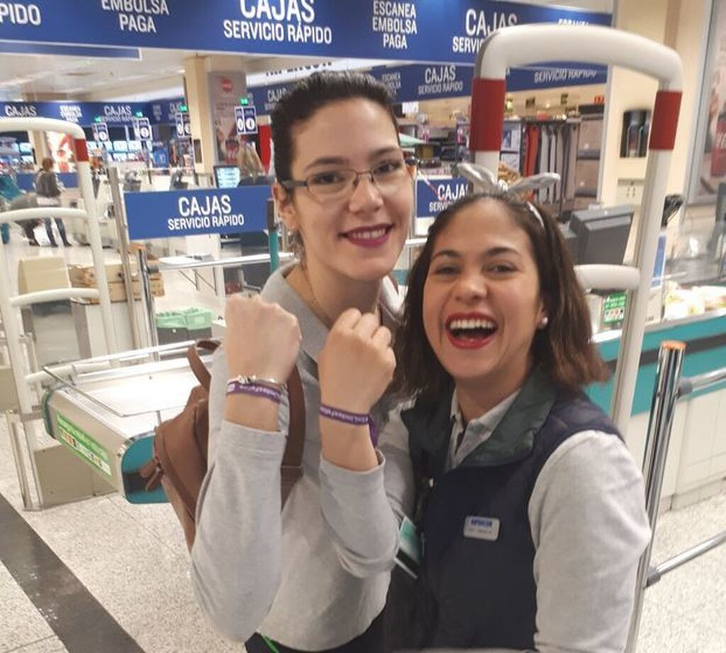 Dos trabajadoras de Hipercor muestran su pulsera por la igualdad