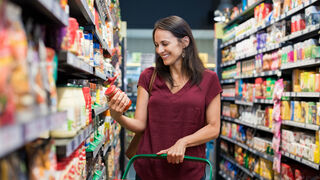 Consumidora revisando la etiqueta de un producto en un supermercado