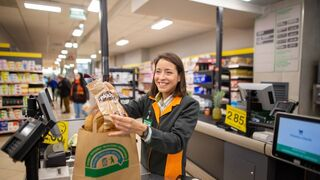 Una empleada de Mercadona introduce varios artículos en una bolsa de papel